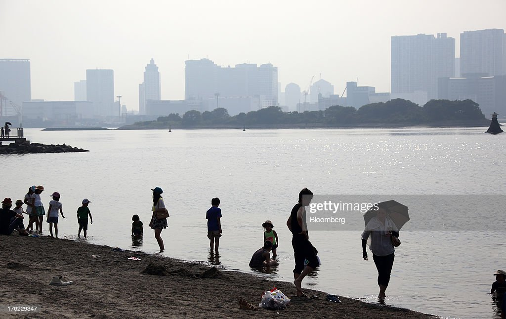 Beachgoers stand on the beach in the Odaiba area of Tokyo, Japan, on Monday, Aug. 12, 2013. Japan's economy slowed more than forecast in the second quarter as businesses cut investment, undermining gains in consumer and government spending that helped reduce deflationary pressures. Photographer: Tomohiro Ohsumi/Bloomberg via Getty Images