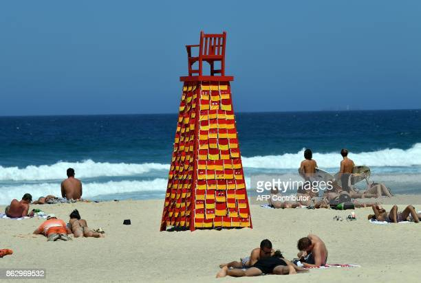 Beachgoers sunbathe next to a sculpture by artist Linton Meagher at the 'Sculpture by the Sea' exhibition near Bondi beach in Sydney on October 19...