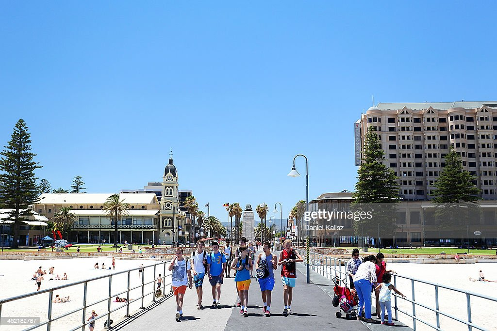Beachgoers visit the Glenelg jetty during a heat wave at Glenelg on January 13, 2014 in Adelaide, Australia. Temperatures are expected to be over 40 degrees celsius all week with health authorities warning the young and elderly to remain indoors.