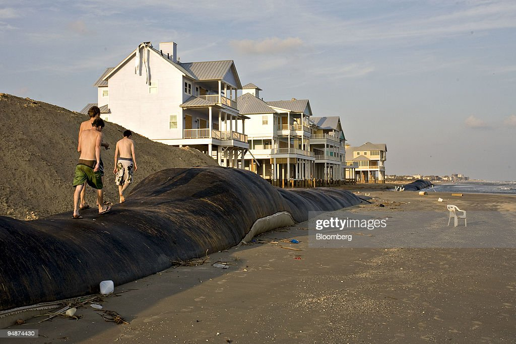 Beach-goers walk atop an artificial sandwall exposed due to erosion following Hurrican Ike on West Beach in Galveston, Texas, U.S., on Saturday, Oct. 11, 2008. Hundreds of thousands of residents throughout the Houston and Galveston region are still assessing damage, some living in motels and shelters while repairs are made, after Hurricane Ike blasted ashore with a storm surge of up to 12 feet last month.