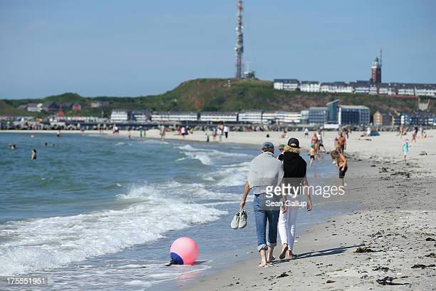Beachgoers walk on the south beach of Duene Island on a hot and sunny day on August 4 2013 near Helgoland Germany Duene Island was once an extension...