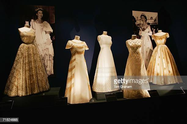 Beaded and embroidered white and gold evening dresses designed by Sir Norman Hartnell for Queen Elizabeth II stand on display at an exhibition of her...