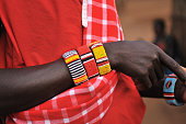 Close-up of hands and beaded bracelets of Masai warrior in traditional red robe