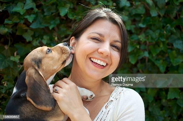 A Beagle licking a woman's ear