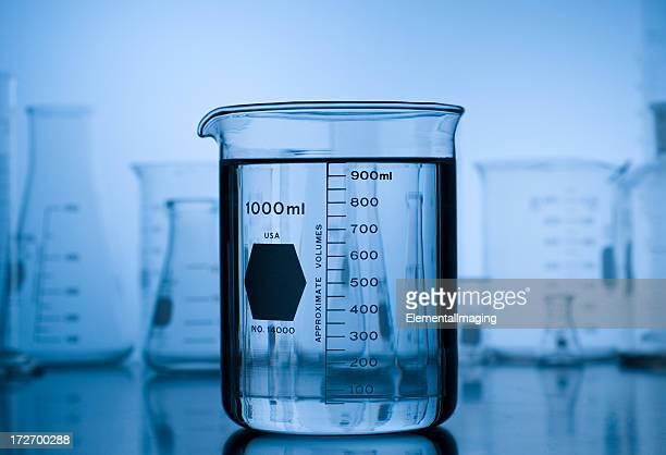 Récipient à bec verseur sur dégradé bleu avec fond de verre de laboratoire
