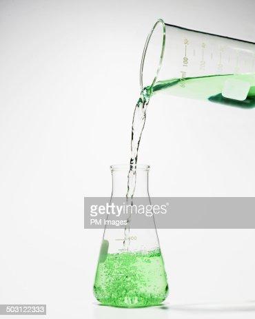 Beaker pouring green liquid into laboratory flask
