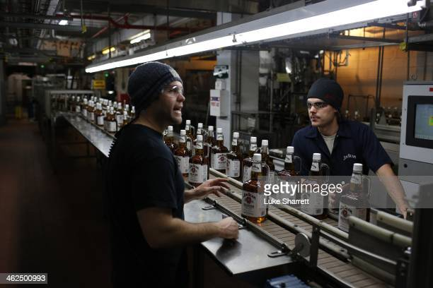 Beam Inc employees Patrick Meredith and Ben Burks converse along a conveyor belt in the bottling plant at the Jim Beam Bourbon Distillery on January...