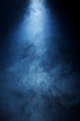 Narrow beam of light passing through blue/grey smoke on a black background. Great used as a dramatic overlay texture or background.