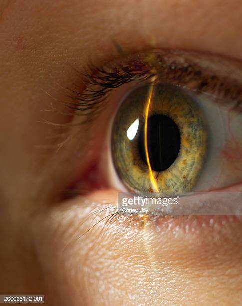 Beam of light shining on woman's eye, close-up