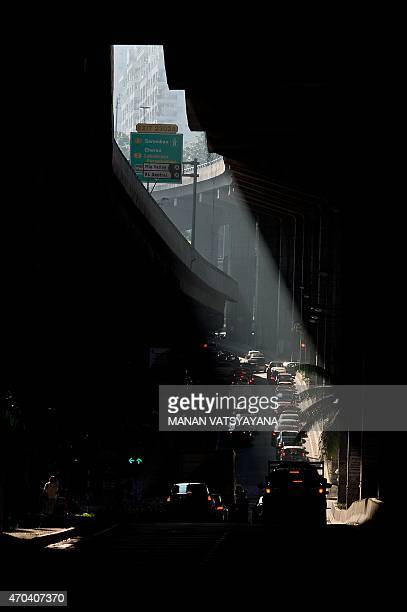 A beam of sunlight falls on rushhour traffic on a road in Kuala Lumpur on April 20 2015 Early morning officegoers experience gridlocked jams on a...