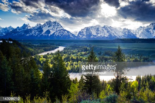 Beams of light penetrate the clouds at the classic Snake River Overlook in Grand Teton National Park, Wyoming.