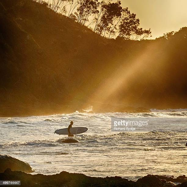 Beams of sunlight shine down on a surfer