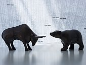 Bear and bull figurines facing each other