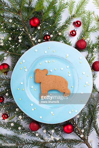Bear gingerbread with decorated fir tree on background