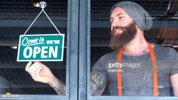 Bearded and tattooed hipster opening the coffee shop