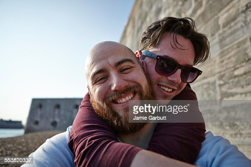 Bearded bald male smiling whilst being hugged