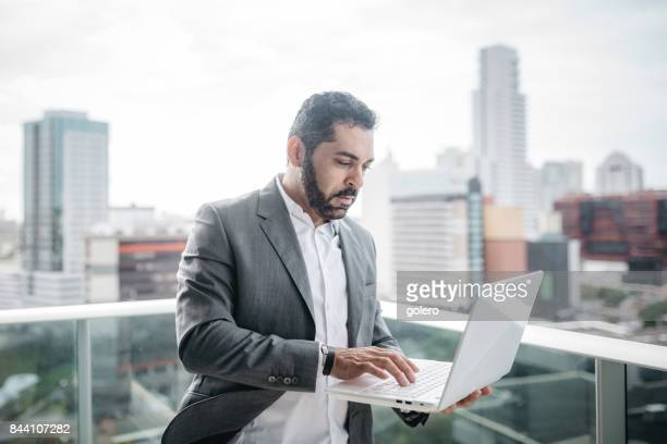 bearded  brazilian businessman with laptop on top of business building