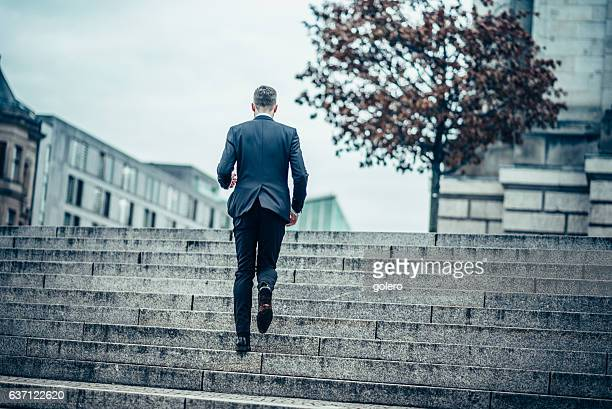 bearded business man running up stone stairway in city
