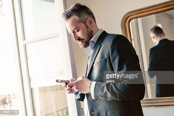 bearded business man with smartphone at opened window