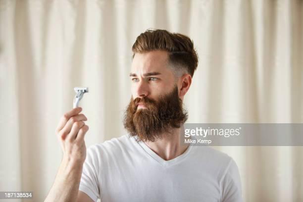 Bearded Caucasian man examining razor