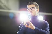 Head and shoulders portrait of confident young designer in eyeglasses holding microphone in hand while making presentation for his colleagues