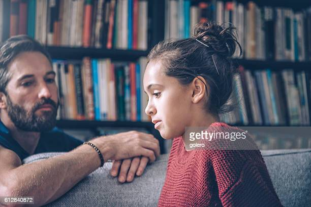 bearded father and daughter looking serious and pensive