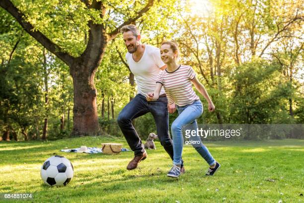 bearded father and teenage daughter playing soccer on meadow in park