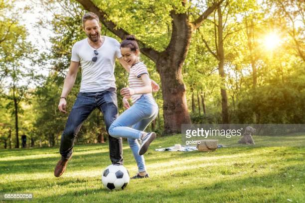 bearded father and teenage daughter playing soccer on summer meadow