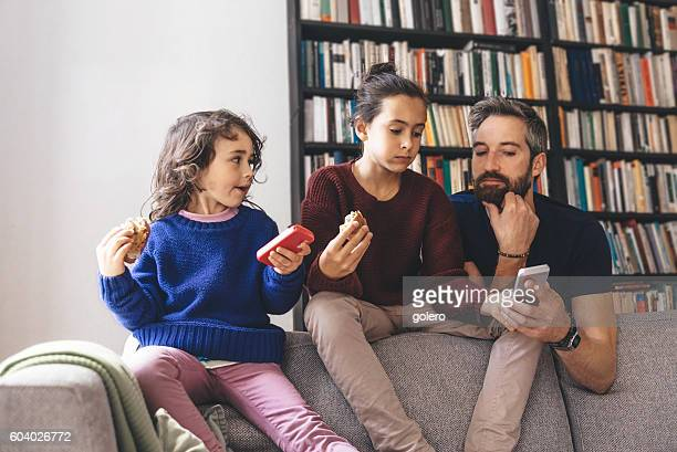bearded father and two daugthers on sofa looking at mobiles
