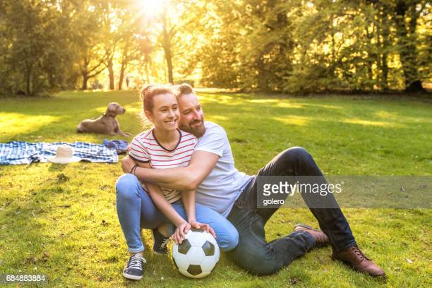 bearded father embracing teenage daughter in park