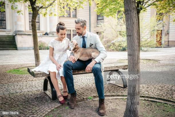 bearded father on bench with festive dressed daughter and dog in Berlin