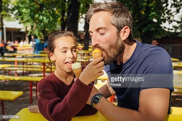 bearded father sharing ice cream with daughter