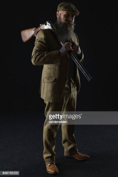 Bearded gentleman in his 50s with a shotgun
