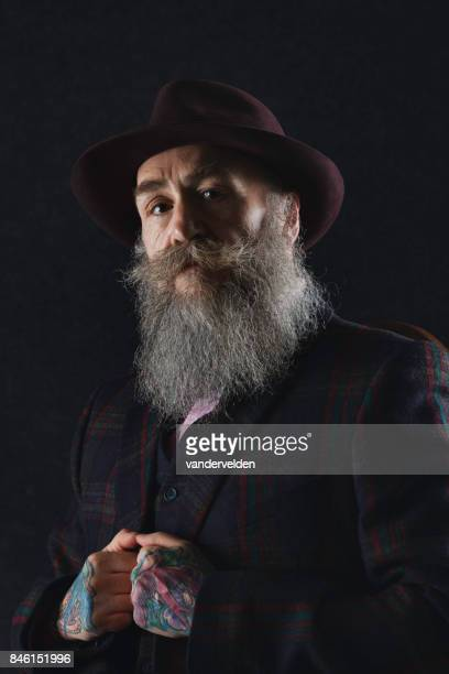 Bearded gentleman in his 50s with tattooed hands