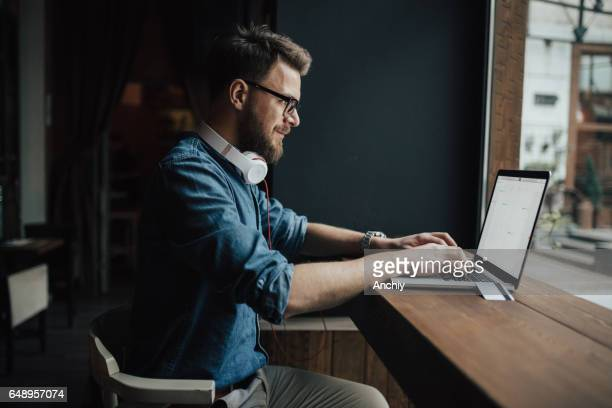 Bearded graphic designer checking schedule on laptop