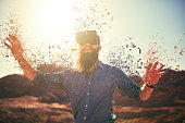 bearded guy in desert wearing vr glasses dissolving into pixels
