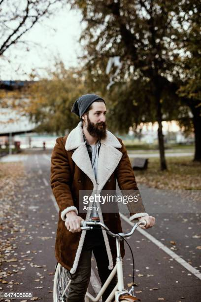 Bearded guy in stylish coat ride a vintage bicycle in the fall