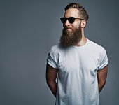 Portrait of handsome single bearded young man with serious expression wearing sunglasses and white short sleeve shirt looking over gray background with copy space