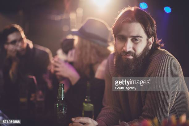 Bearded hipster in the bar with friends