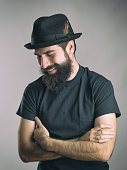 Bearded hipster wearing black t-shirt and hat laughing spontaneous with closed eyes. Retro toned filtered portrait over gray background with vignette effect