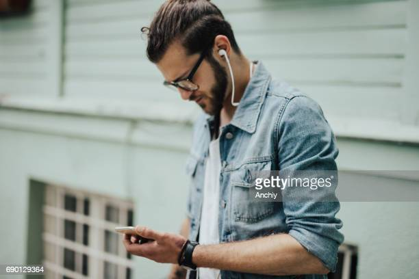 Bearded hipster listens to podcast over the smartphone