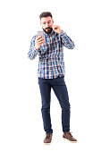Bearded hipster man twirling mustache using mobile phone reflection as mirror. Full body isolated on white background.