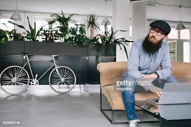 Bärtiger hipster sitzt auf der couch und arbeiten auf laptop-Computer