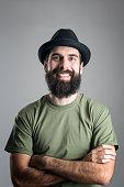 Bearded hipster wearing hat with upper lips piercing friendly laughing at camera. Headshot portrait over gray studio background with vignette.