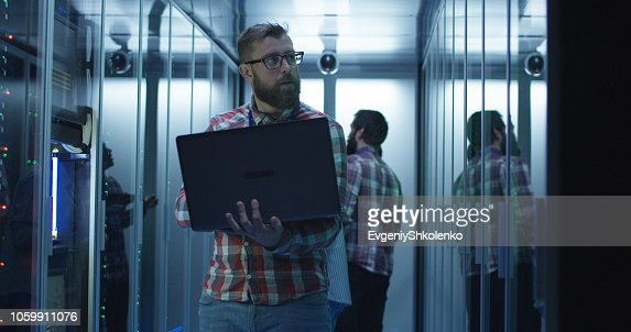 Bearded IT engineer using laptop in server room : Stock Photo