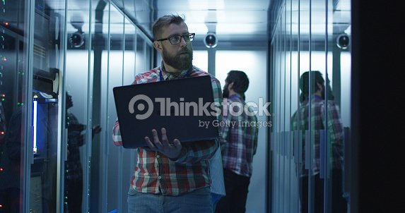 Bearded IT engineer using laptop in server room : Stock Photo