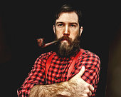 A man dressed as a lumberjack with a plaid shirt and suspenders has a big beard and a pipe in his mouth.