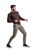 A bearded man a jumper and pants tries to pull a strong invisible rope on a white background. Test of strength. Heavy catch. Pull rope.