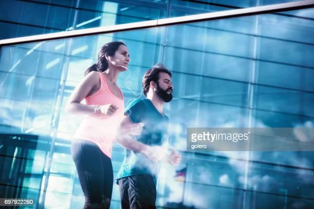bearded man and latina sportswoman running in city