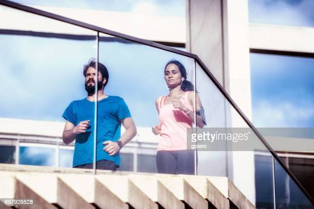 bearded man and latina sportswoman running on stairs in city
